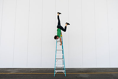 Acrobat balancing upside down on a ladder - p300m2012354 by VITTA GALLERY
