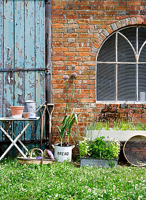 Gardening tools at brick exterior with arched window and weathered door;  Isle of Wight;  UK - p349m920084 by Rachel Whiting