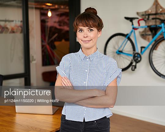 Junge Frau im Büro mit Laptop - p1124m1150220 von Willing-Holtz
