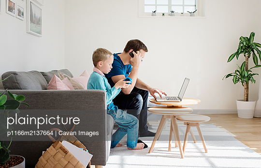father sat at home with his son on his mobile and laptop - p1166m2137664 by Cavan Images