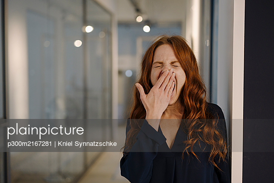 Redheaded woman yawning on office floor - p300m2167281 by Kniel Synnatzschke