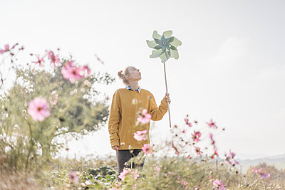 Young woman with pinwheel in cottage garden - p300m1205393 by Kniel Synnatzschke