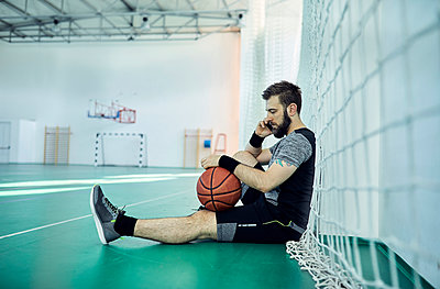 Man with basketball using smartphone, indoor - p300m1587462 by Zeljko Dangubic