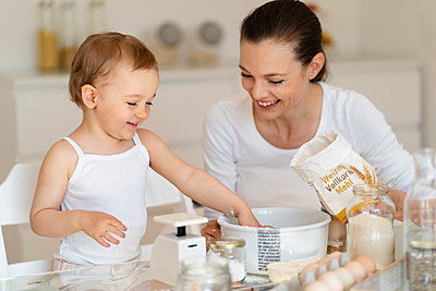 Happy mother and little daughter making a cake together in kitchen at home - p300m2102618 by Daniel Ingold
