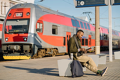 Stylish man reading documents while waiting for the train - p300m2154614 by Hernandez and Sorokina