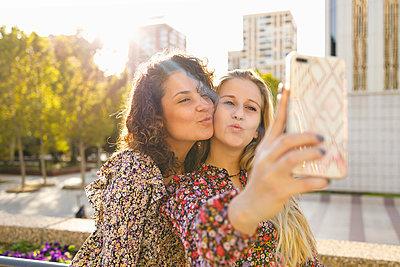 Female friends puckering while taking selfie through smart phone on sunny day - p300m2240804 by Ignacio Ferrándiz Roig