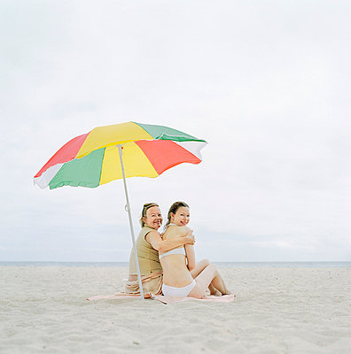 Rear view of a mature woman sitting with her daughter on the beach - p3741548 by Karin Smeds
