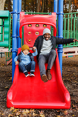 Father and son on playground slide in park - p555m1219614 by Roberto Westbrook