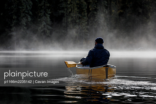Bearded man solo paddling on a calm misty lake in a yellow canoe - p1166m2235142 by Cavan Images