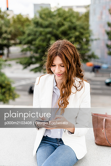 Young businesswoman commuting in the city, using smartphone - p300m2103408 by Giorgio Fochesato