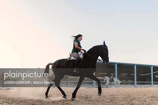 Mid adult woman riding horse by clear sky in farm during weekend - p300m2256328 by Manu Reyes