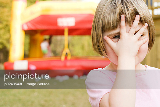 Girl with hand in front of face - p9249543f by Image Source