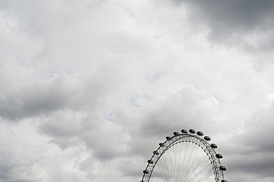 Low angle view of millennium wheel against cloudy sky - p1166m1204242 by Cavan Images