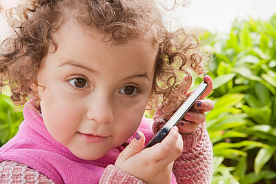 Curious girl listening to smart phone - p1427m2077559 by REB Images