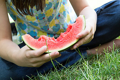 Girl eating slice of watermelon in the garden, partial view - p300m949943f by Larissa Veronesi