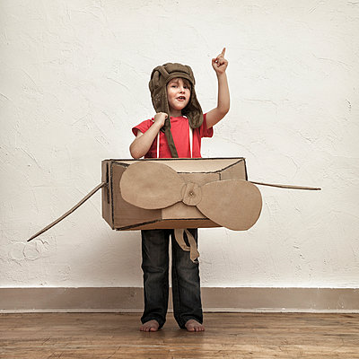 Little boy playing with pilot hat and cardboard box aeroplane - p300m978713f by Mimafoto