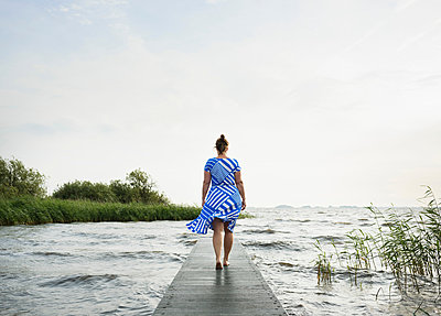 Woman posing in the Frisian lake district in vintage dress, Sneek, Friesland, Netherlands - p429m1494189 by Mischa Keijser