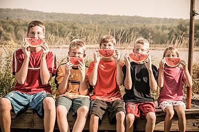 Caucasian children eating watermelon outdoors - p555m1454159 by Jon Feingersh