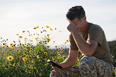 Soldier wearing combat clothing looking at smartphone, Runyon Canyon, Los Angeles, California, USA - p924m1422793 by Raphye Alexius