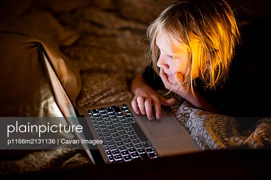 Kid using laptop computer in bed - p1166m2131136 by Cavan Images