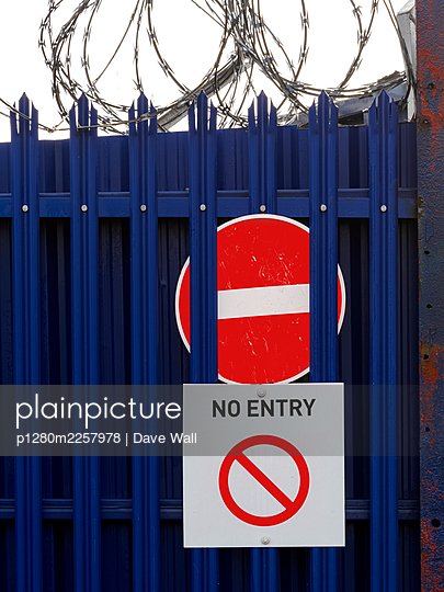 No entry signs on security fence with barbed wire - p1280m2257978 by Dave Wall