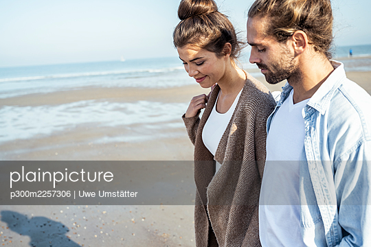 Young couple walking on beach during sunny day - p300m2257306 by Uwe Umstätter