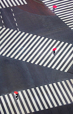 High angle view of three people carrying bright red umbrellas walking across urban street at pedestrian crossings. - p1100m1570989 by Mint Images