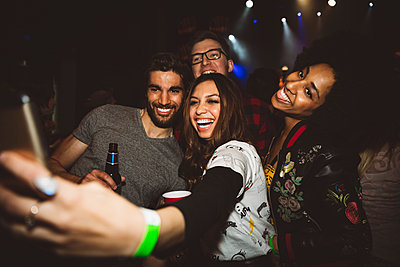 Playful, happy millennial friends taking selfie with camera phone, partying in nightclub - p1192m1567119 by Hero Images
