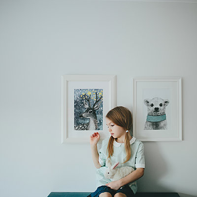 Girl sitting in front of framed pictures - p1414m1590578 by Dasha Pears