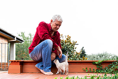 Senior man with kitten sitting on roof terrace - p300m2139569 by VITTA GALLERY