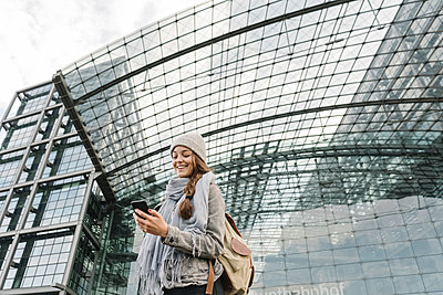 Happy young woman using smartphone at the central station, Berlin, Germany - p300m2154548 by Hernandez and Sorokina