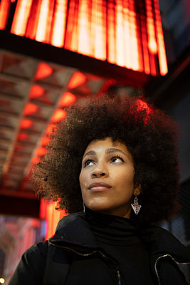 Afro woman looking up while day dreaming in city at night - p300m2242920 by Ignacio Ferrándiz Roig