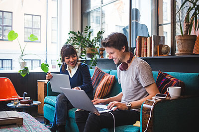 Smiling multi-ethnic male and female professionals discussing over laptop on sofa at office - p426m2089004 by Maskot
