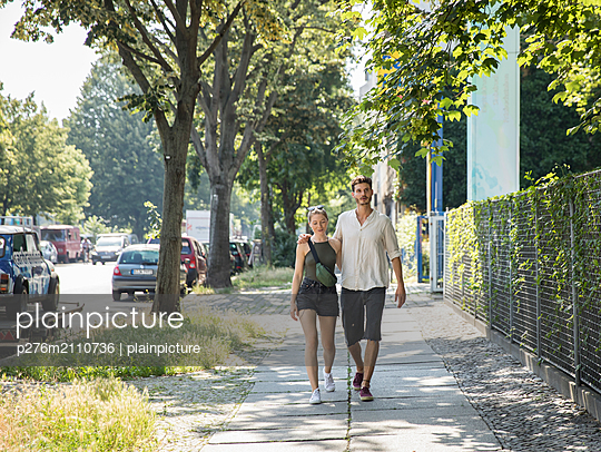Couple is walking on sidewalk - p276m2110736 by plainpicture