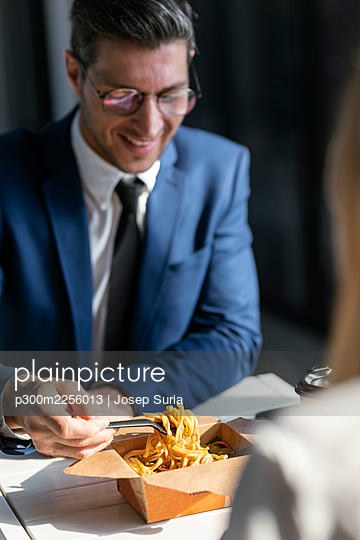 Businessman eating food while sitting with colleague in cafeteria at office - p300m2256013 by Josep Suria