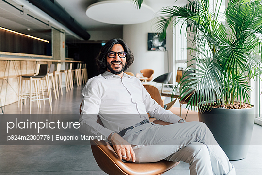 Italy, Portrait of smiling man sitting in armchair in creative studio - p924m2300779 by Eugenio Marongiu