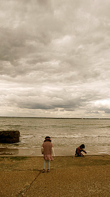 Children on a beach beneath a cloudy sky - p1072m829533 by Tracy Jean Shields