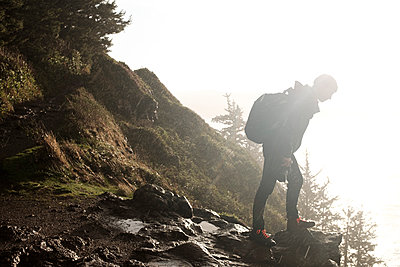 Side view of hiker with backpack standing on rocks against clear sky during rainfall - p1166m1546869 by Cavan Images