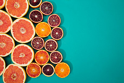 Overhead view of various citrus fruits on blue background - p1166m1566909 by Cavan Images