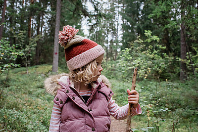 young girl stood in a forest looking at her walking stick thinking - p1166m2136857 by Cavan Images