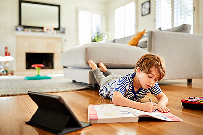 Boy lying on hardwood floor while coloring in book with crayon at home - p1166m2285862 by Cavan Images