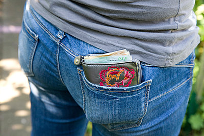 Cash stuffed wallet in back pocket - p1231m1043165 by Iris Loonen