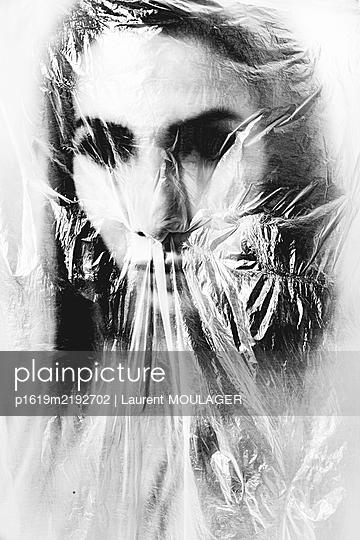 Female portrait hidden behind a plastic wrap - p1619m2192702 by Laurent MOULAGER