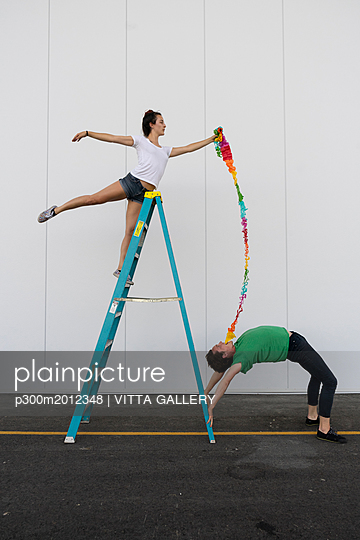 Two acrobats exercising trick on a ladder with a ribbon - p300m2012348 von VITTA GALLERY