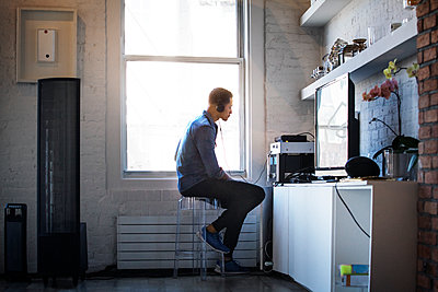 Side view of man listening music while sitting by window at home - p1166m1150851 by Cavan Images