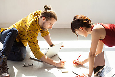 Business people writing in notes on floor at brightly lit creative office - p1166m1534400 by Cavan Images