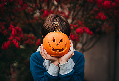Young boy holding a mini jack-o-lantern over his face outdoors. - p1166m2224119 by Cavan Images