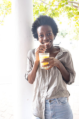 Young African woman has a soft drink - p1640m2260097 by Holly & John