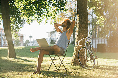 Man with beard and curly hair using laptop in park - p300m1469634 by Kniel Synnatzschke