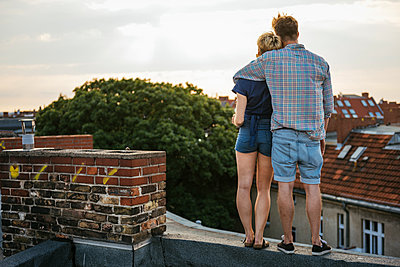 Germany, Berlin, Young couple standing on rooftop looking at view - p352m1127283f by Lars Hollander